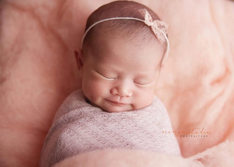 15 days old baby girl with dimple on log bed newborn portraits in singapore studio